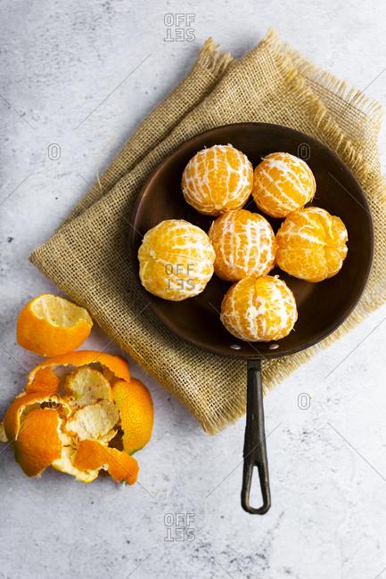 Freshly peeled mandarines�on frying pan