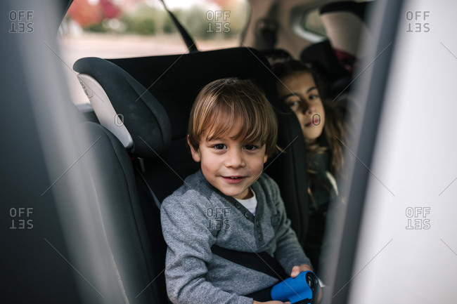 Portrait of smiling little boy sitting in child's seat in car