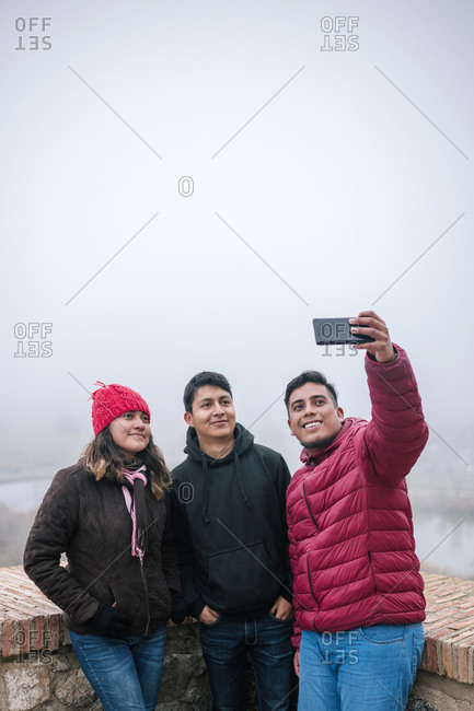 Young Mexican friends taking a selfie on a foggy day-  Toledo- Spain