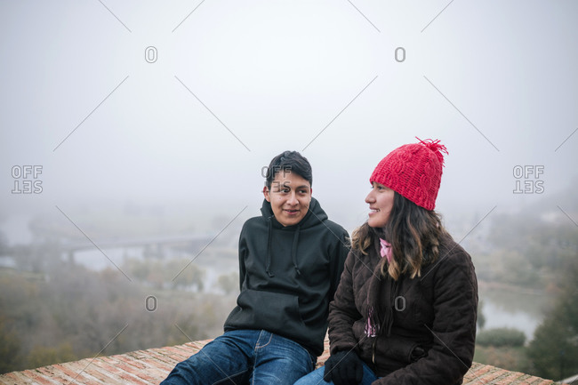 Young Mexican couple interacting on a foggy day