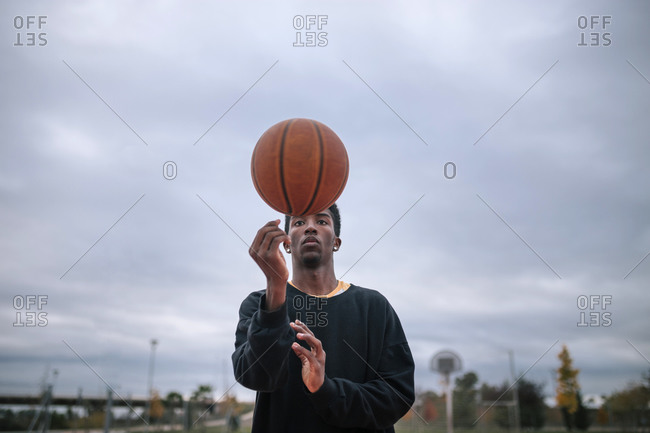 Teenager balancing basketball on his finger
