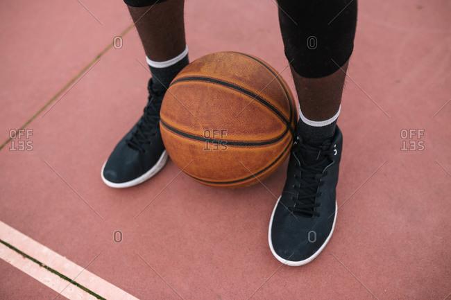 Basketball between feet of basketball player