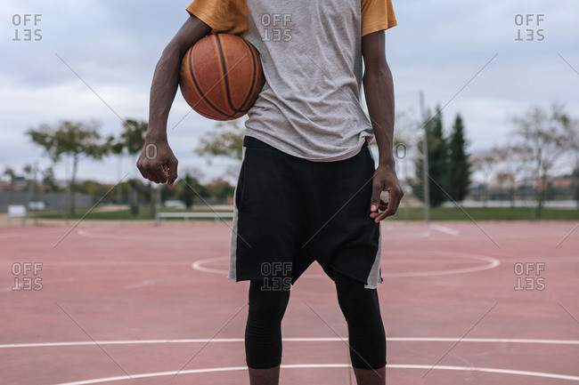 Teenager holding basketball with his arm
