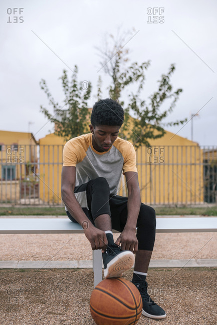 Teenager with basketball- tying shoes