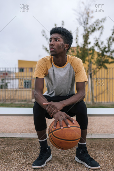 Teenager holding basketball and looking sideways