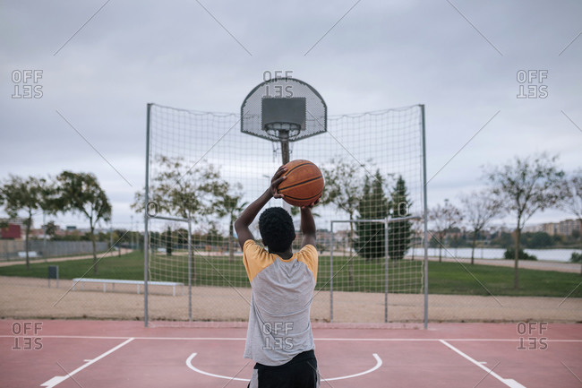 Rear view of teenager playing basketball