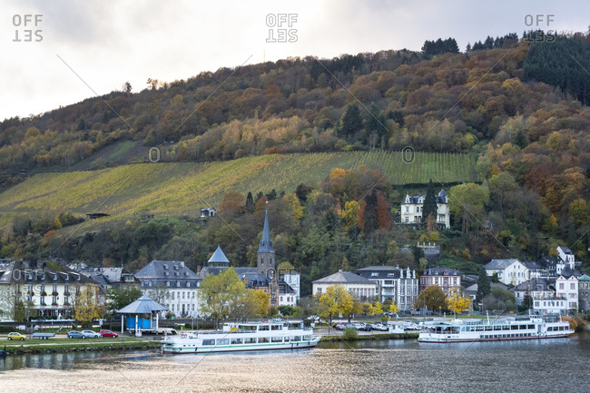 November 12, 2019: Germany- Rhineland-Palatinate- Traben-Trarbach- Ferries moored in front of houses of riverside town with hillside vineyard in background