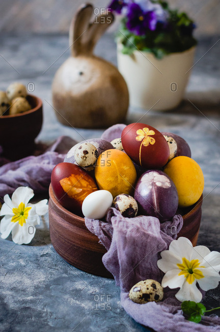 Naturally dyed Easter eggs on wooden bowl, front view