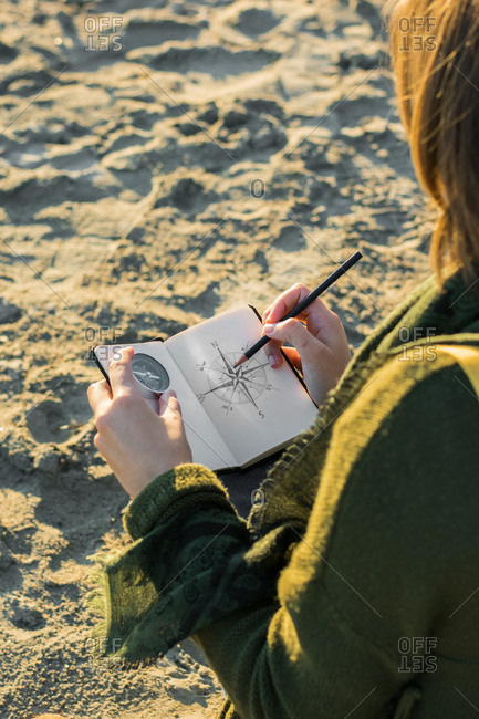 Young woman is drawing a compass in a notebook.