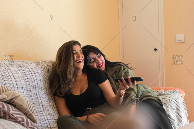 Two young women are looking the tv on the couch of her house