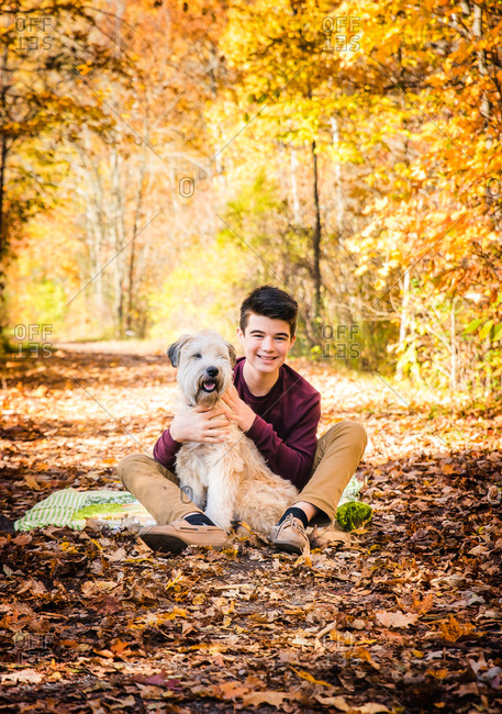 Teenage boy sitting with dog on leafy trail in the woods on fall day.