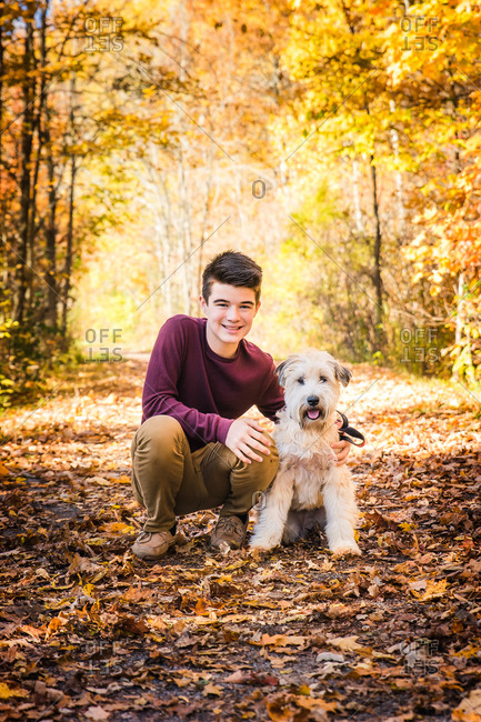 Teenage boy with furry dog on leafy trail in the woods on fall day.
