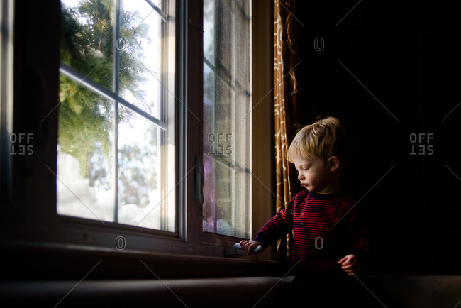 A little boy tries to open a window.