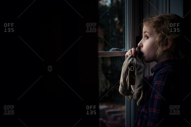 A little girl sucking her thumb looks out her front door.