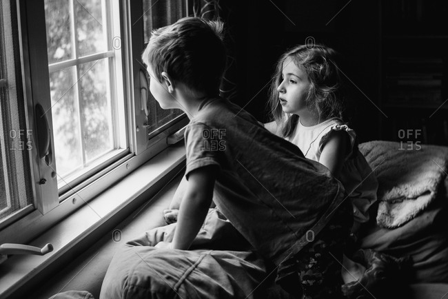 Two children perch on a couch and look out a window.