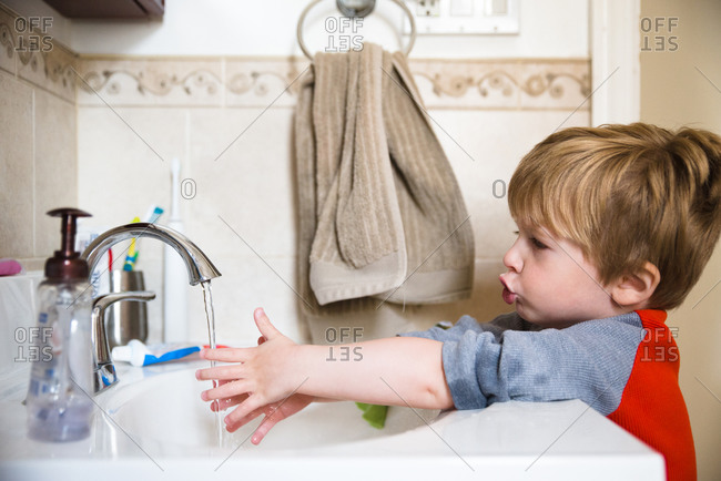 A little boy washes his hands in the bathroom sink.