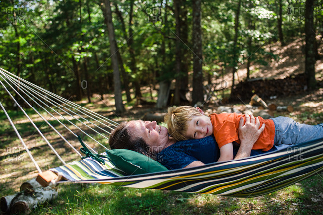 A little boy lies with his grandmother in a hammock.