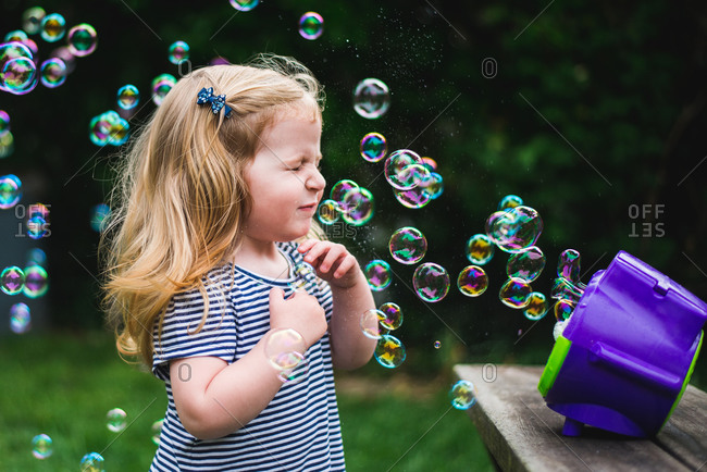 A little girl stands in front of a bubble machine.