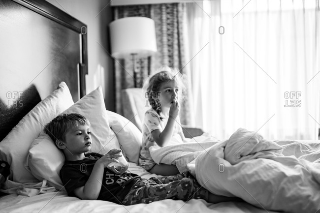 Two children lie in a hotel room bed eating snacks.