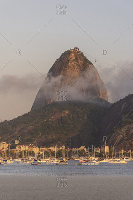 Brazil, State of Rio de Janeiro, Rio de Janeiro - November 4, 2019: Beautiful view to rocky sugar loaf mountain with pink sunset clouds