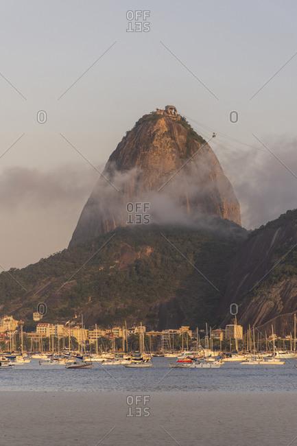 Brazil, State of Rio de Janeiro, Rio de Janeiro - November 4, 2019: Beautiful view to rocky sugar loaf mountain with pink sunset clouds