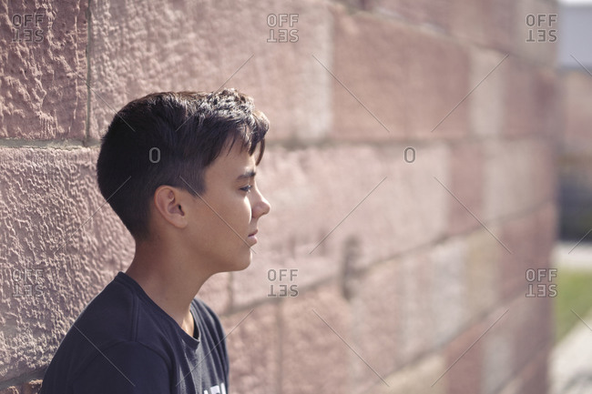 Teen on the street in a sunny day. pink wall