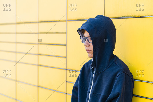 Teen with eyeglasses in a yellow background