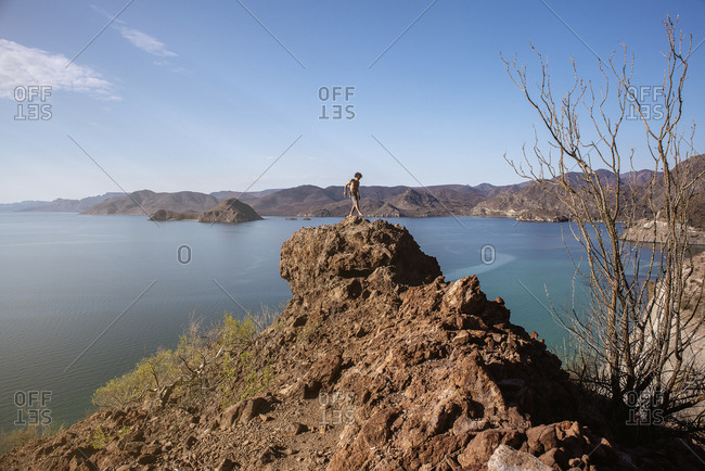 Baja traveler standing on a rocky cliff