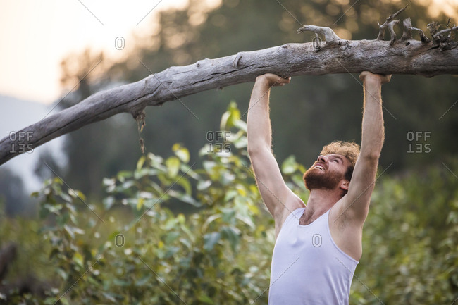 Man shoulder presses a fallen tree outside in nature's gym.
