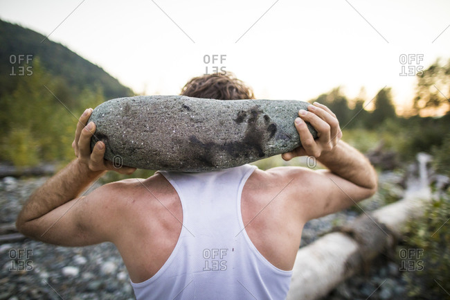 Rear view of man using large rock as part of an outdoor workout.