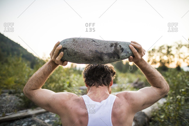 Rear view of man lifting rock above head during an outdoor workout.