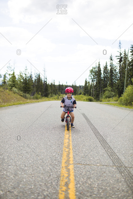 Toddler boy biking on balance bike in middle of the road.