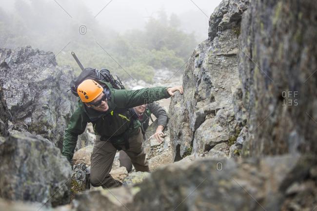 Climber scrambles up a rocky gully in the coast mountain range.