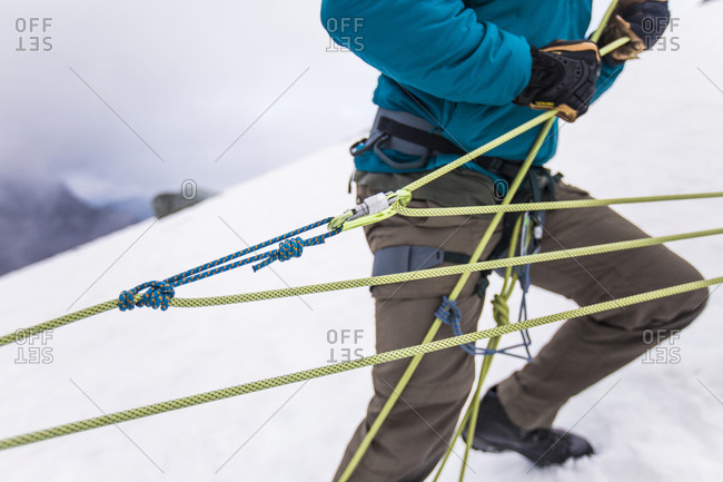 Mountaineer using z-haul to pull climber out of crevasse in mountains.