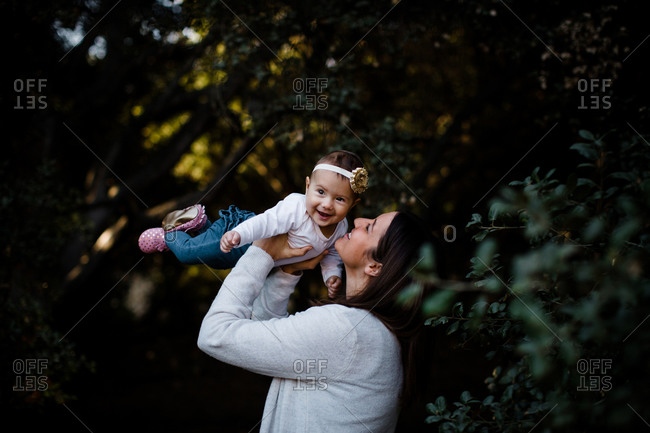 Mom lifting daughter as baby smiles