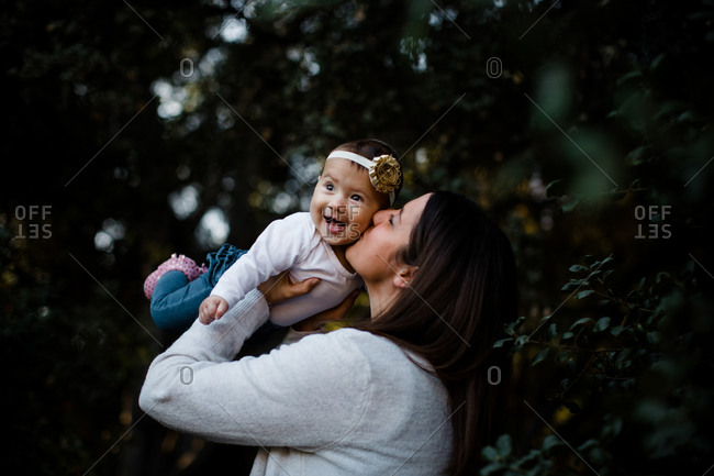 Mom kissing daughter as baby laughs