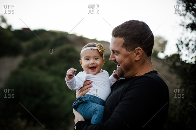 Dad holding infant daughter as baby smiles