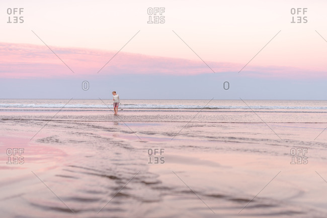Girl with net walking in water on beach at dusk