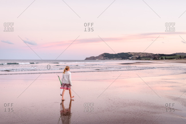 Tween girl at beach with pink sunset and reflection