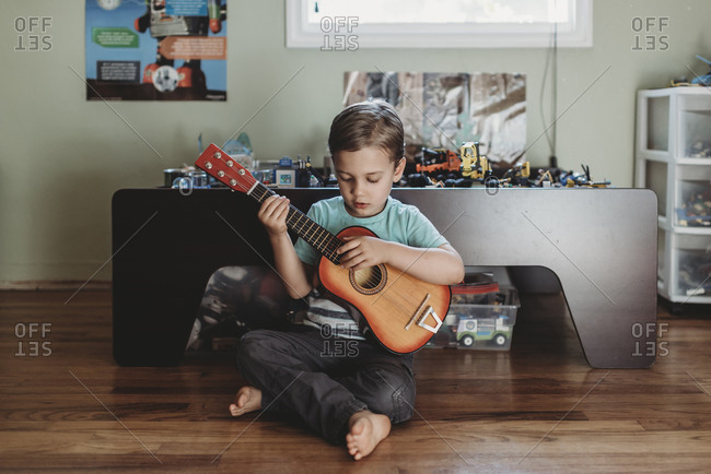 5 yr old boy sitting on hardwood floor playing guitar