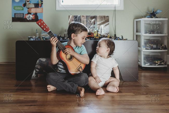 Baby sister and big brother with guitar sitting on hardwood floor