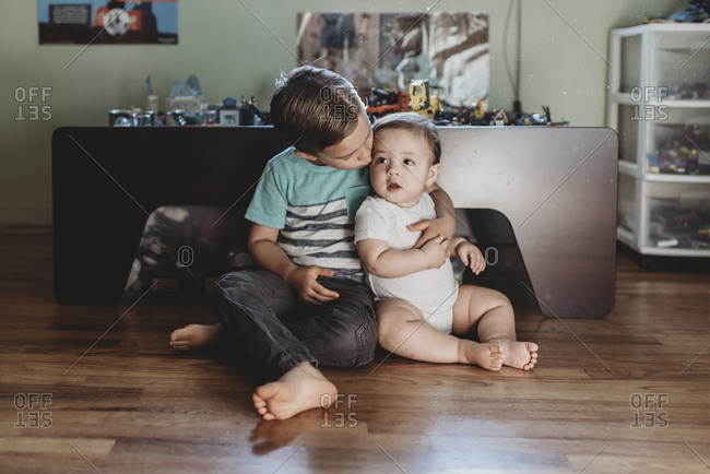 5 yr old boy holding baby sister while sitting on hardwood floor