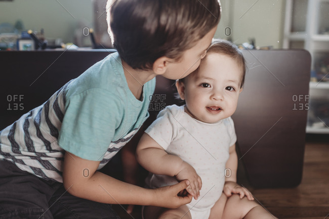 Young boy gently kissing baby sister and holding her tiny hand