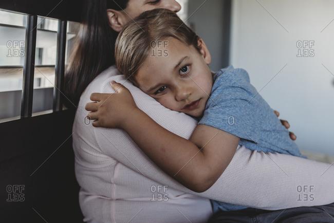 Loving mom cuddling 5 yr old son with big brown eyes