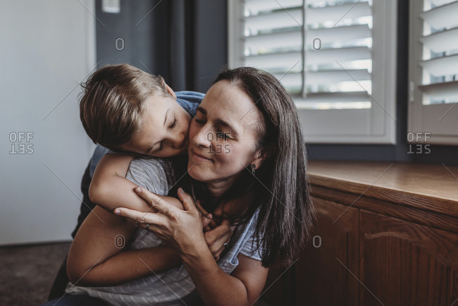 Loving hug between mid-40s mom and 5 yr old son near widow shutters