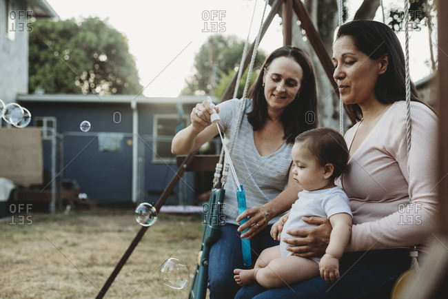 Baby girl on swing with two moms watching bubbles