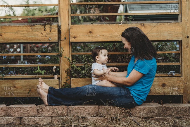 Smiling mom holding baby on outstretched legs in front of fence