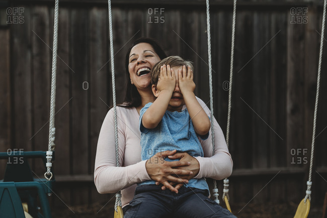 Young boy on swing with laughing mom covers his eyes