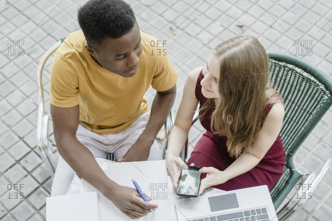 Couple of boy and girl talking and studying on the terrace of a bar