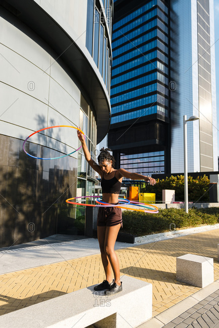Mixed race young woman looking at camera holding hula hoop in city